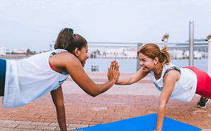 women doing yoga exercise at the beach, working together toward a common goal