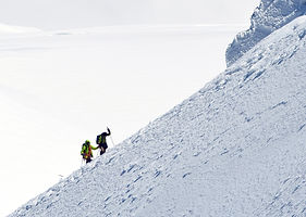 Two people climbing up a snowy mountain that seems to have no top
