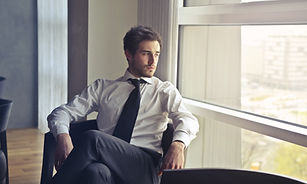 businessman sitting in office chair looking out window