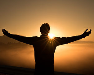 Silhouette of the back of a man standing outside at a great height with both arms stretched out looking out over the tops of mountains while the sun sets