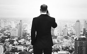 CEO looking out over tall city office buildings while on the phone