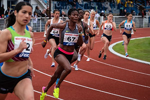 Professional athletes running on a track competing in a race