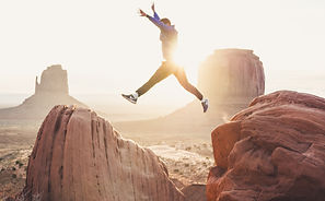 Athlete leaping from one rock to the next