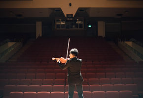 Musician practicing his violin to empty audience seats