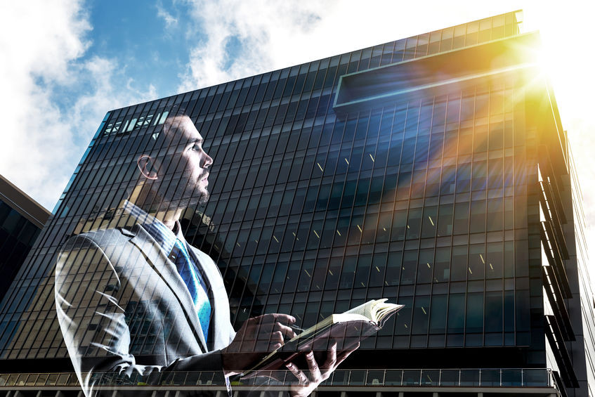 Businessman looking up at reflection of sun in tall corporate building