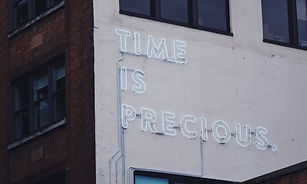 """Façade of a corporate building that has """"TIME IS PRECIOUS"""" written in neon lights on the wall"""