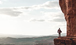 Person standing on ledge of a cliff looking out