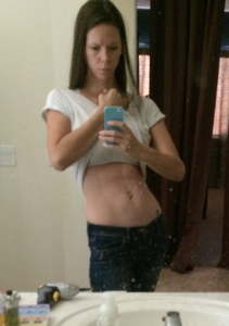 Woman poses in mirror with exposed midriff showing abdominal muscles.