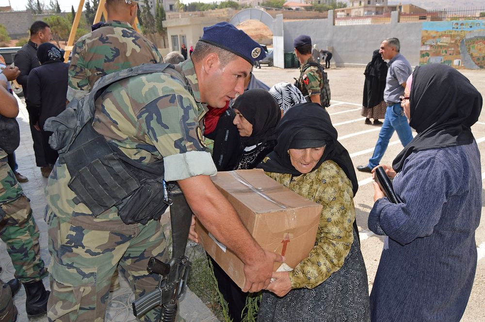 Lebanese soldiers providing food to families in need. Image courtesy of Spirit of America.