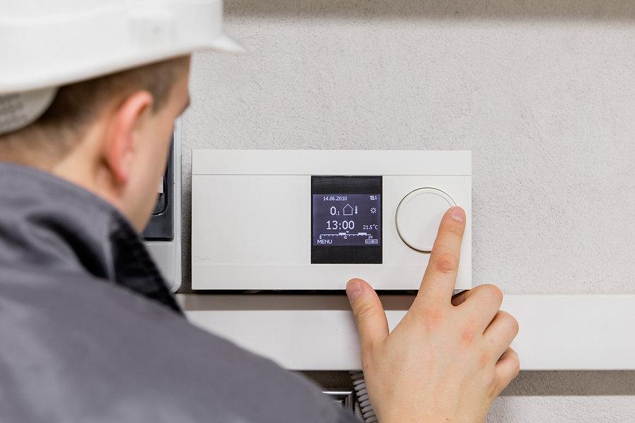 Engineer adjusting thermostat for effici