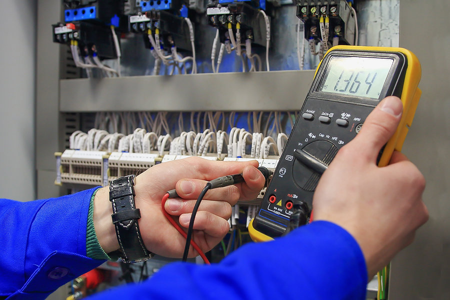 Electrician measures voltage with multim