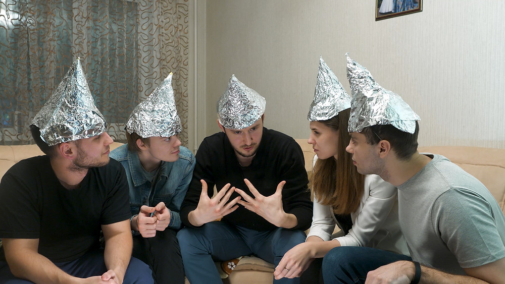 Five people sitting around in a living room with tin foil hats on having a discussion.