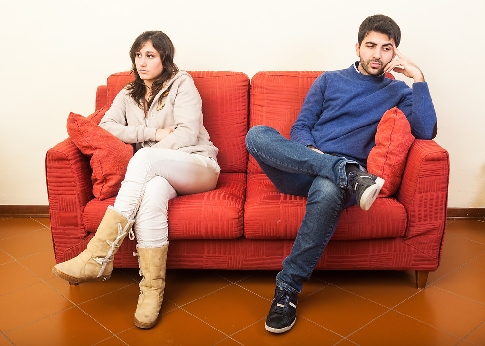 Couple sitting on couch in disagreement.