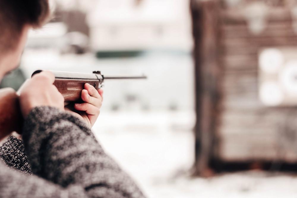 Man shooting at target with rifle
