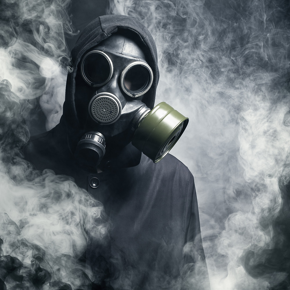 A person wearing a gas mask with smoke all around.