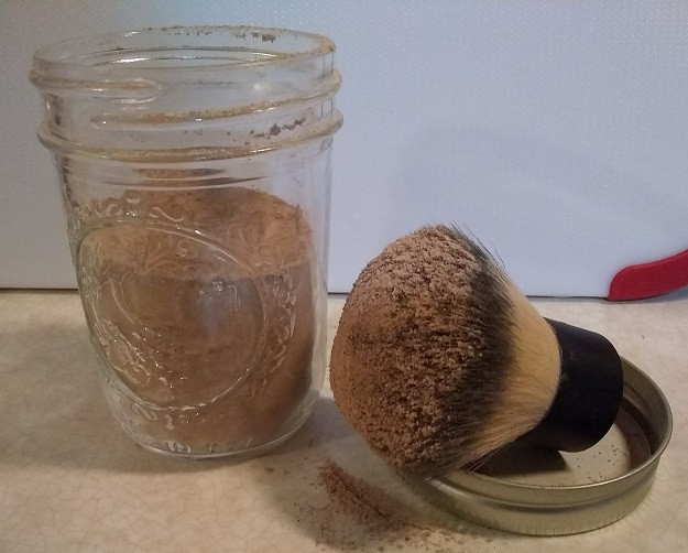 Small jar of DIY dry shampoo with makeup brush for applying.