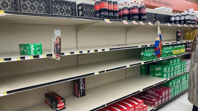 Near empty grocery shelves of soda pop.