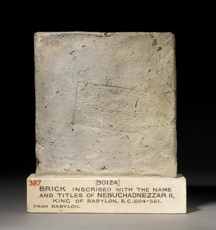 Fired clay brick of Nebuchadnezzar II; six lines of inscription in stamp on face; hard fired to greenish colour; traces of bitumen on the uninscribed side, up to 1 cm thick.