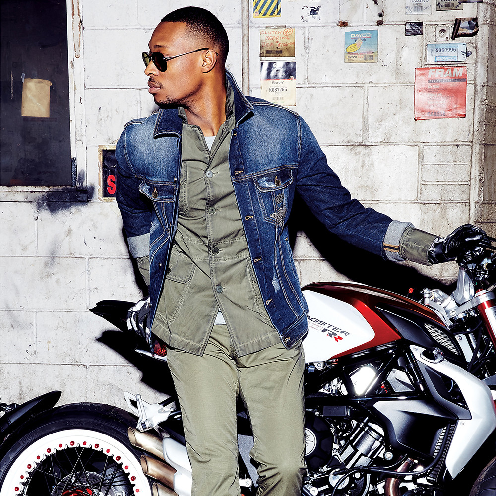 Stylish man in jean jacket by motorcycle