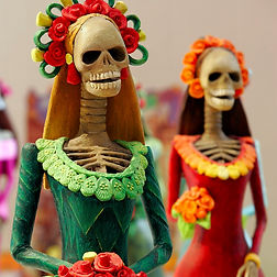 [An image of two small sculptures of La Calavera Catrina: one wearing green, the other wearing red, both with flowers in their hair and holding a bouquet of flowers.]