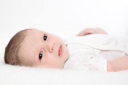 Newborn baby lying on his back looking to the side with wide awake eyes