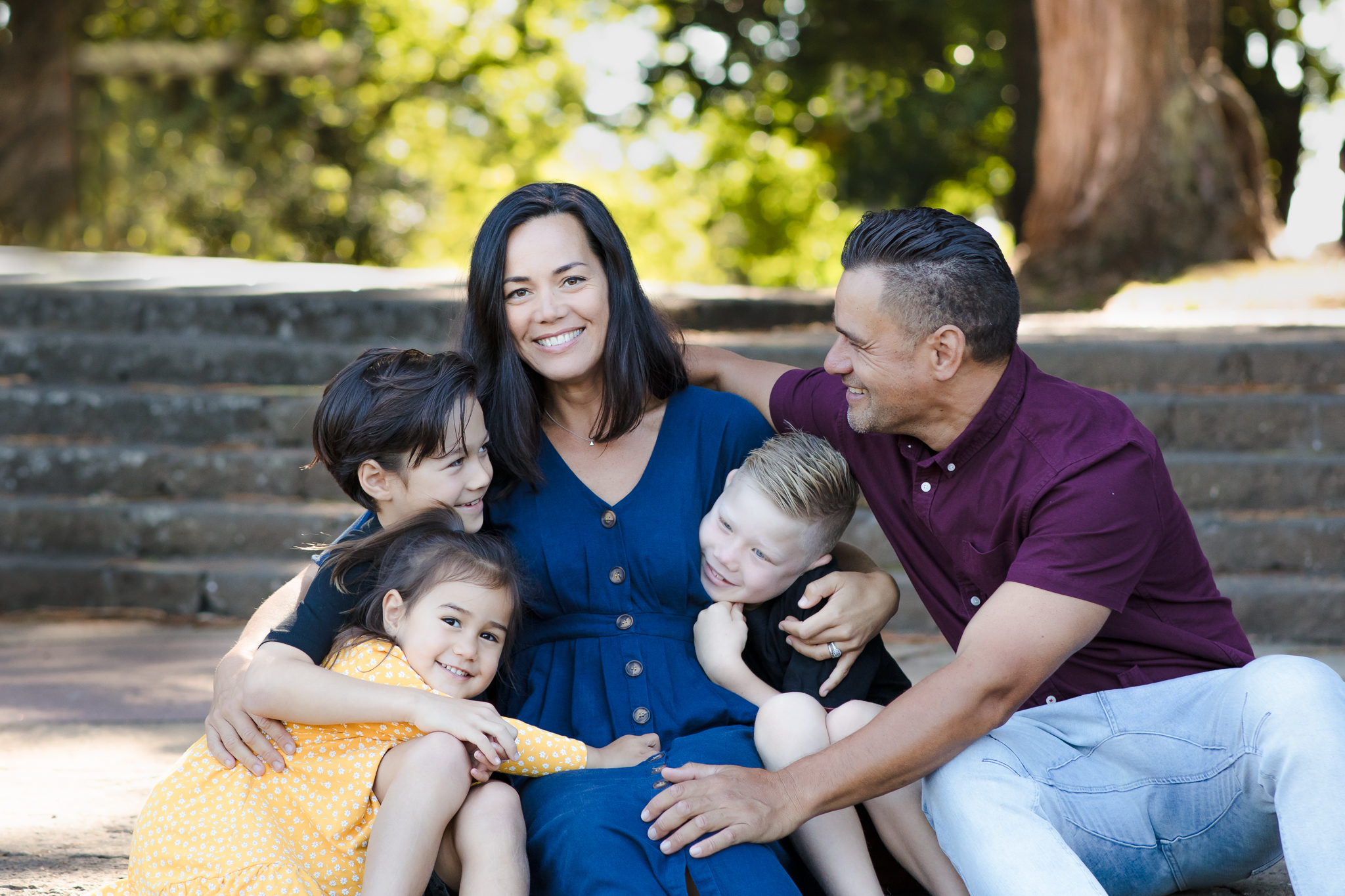 Family of five sit on steps at Cornwall Park