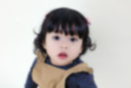 Beautiful toddler looking straight at the camera in a wonderous way taken by Janine Fox photography
