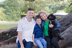 Mum, dad, son and their dog look at the the camera while sitting on a large tree brance