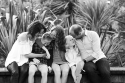 Family cuddle up to each other and laugh while sitting on a bridge, taken by Auckland photographer J