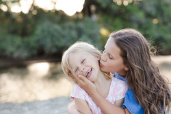 Big sister kissing little sister on the cheek at Long Bay beach Auckland by Janine Fox photography