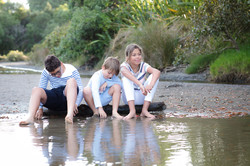 Three children sitting by some water taken at Long Bay, Auckland by Janine Fox photography