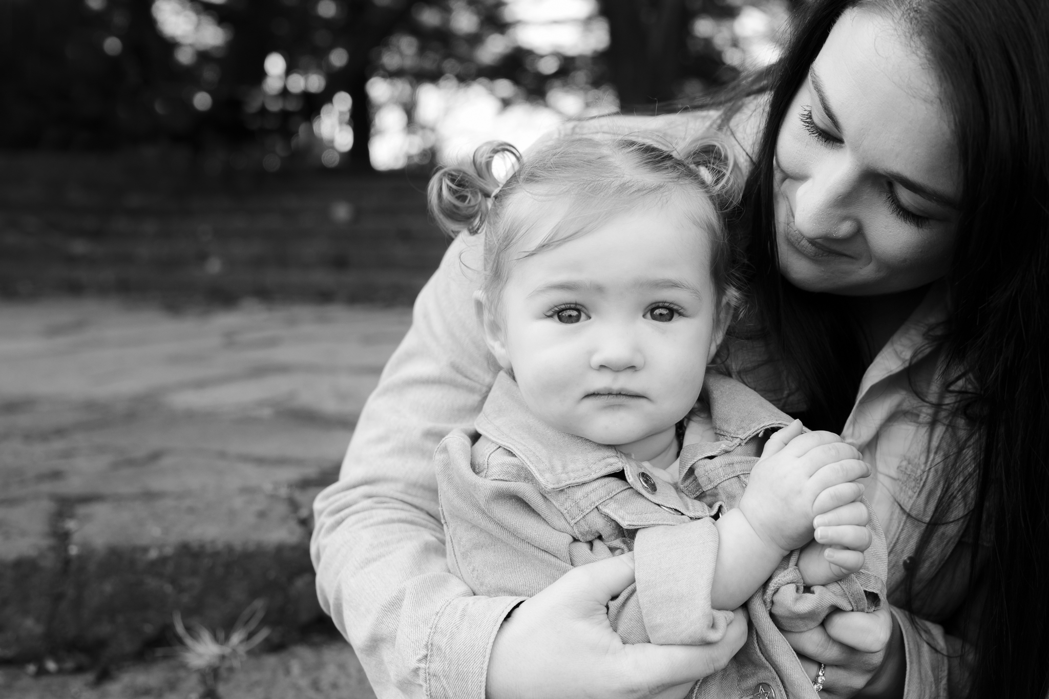 Toddle sitting on Mum's knee looking at the camera at Cornwall Park, Auckland