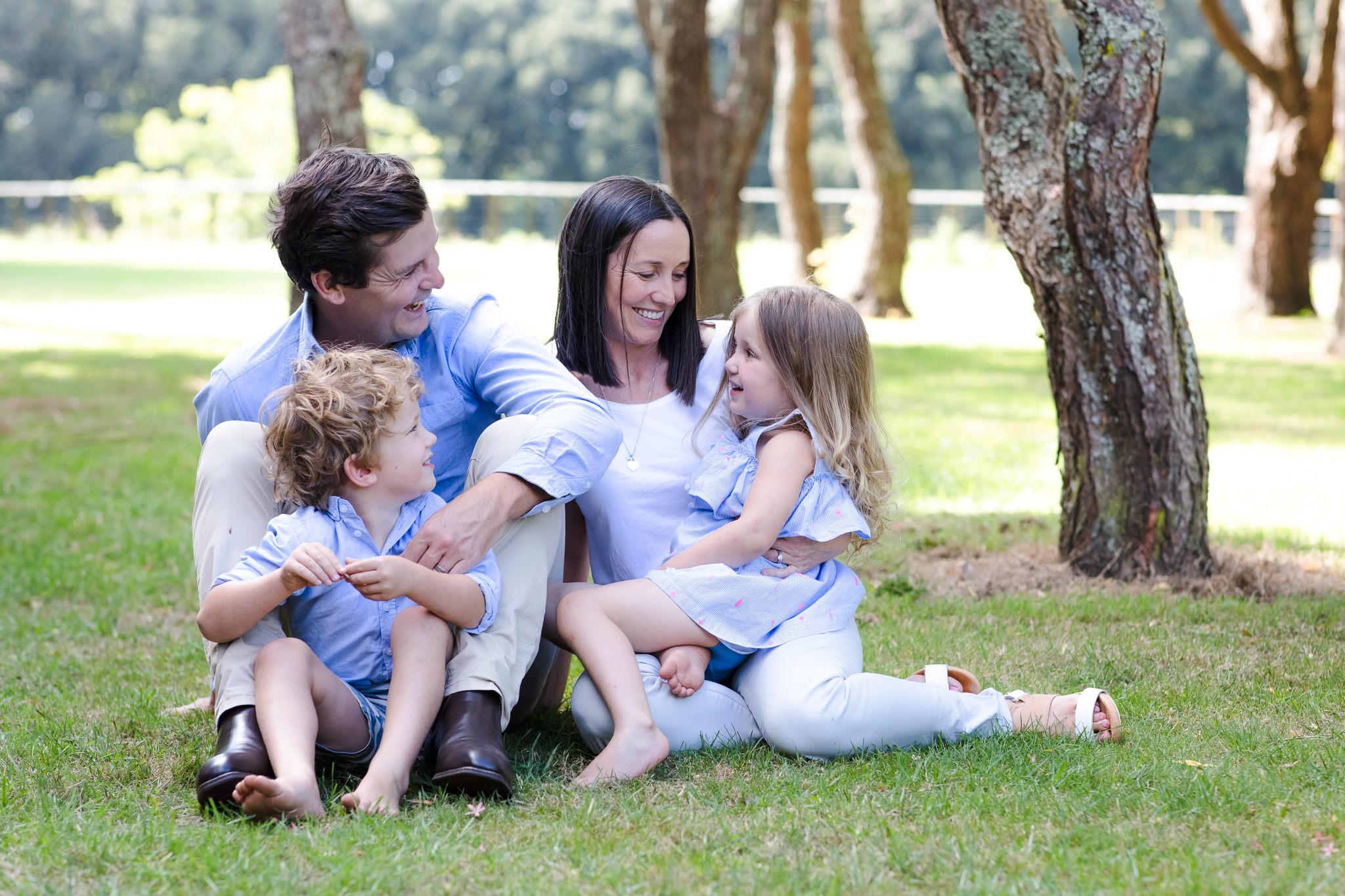 Mum, Dad and two children sit together on the grass at Cornwall Park, Auckland