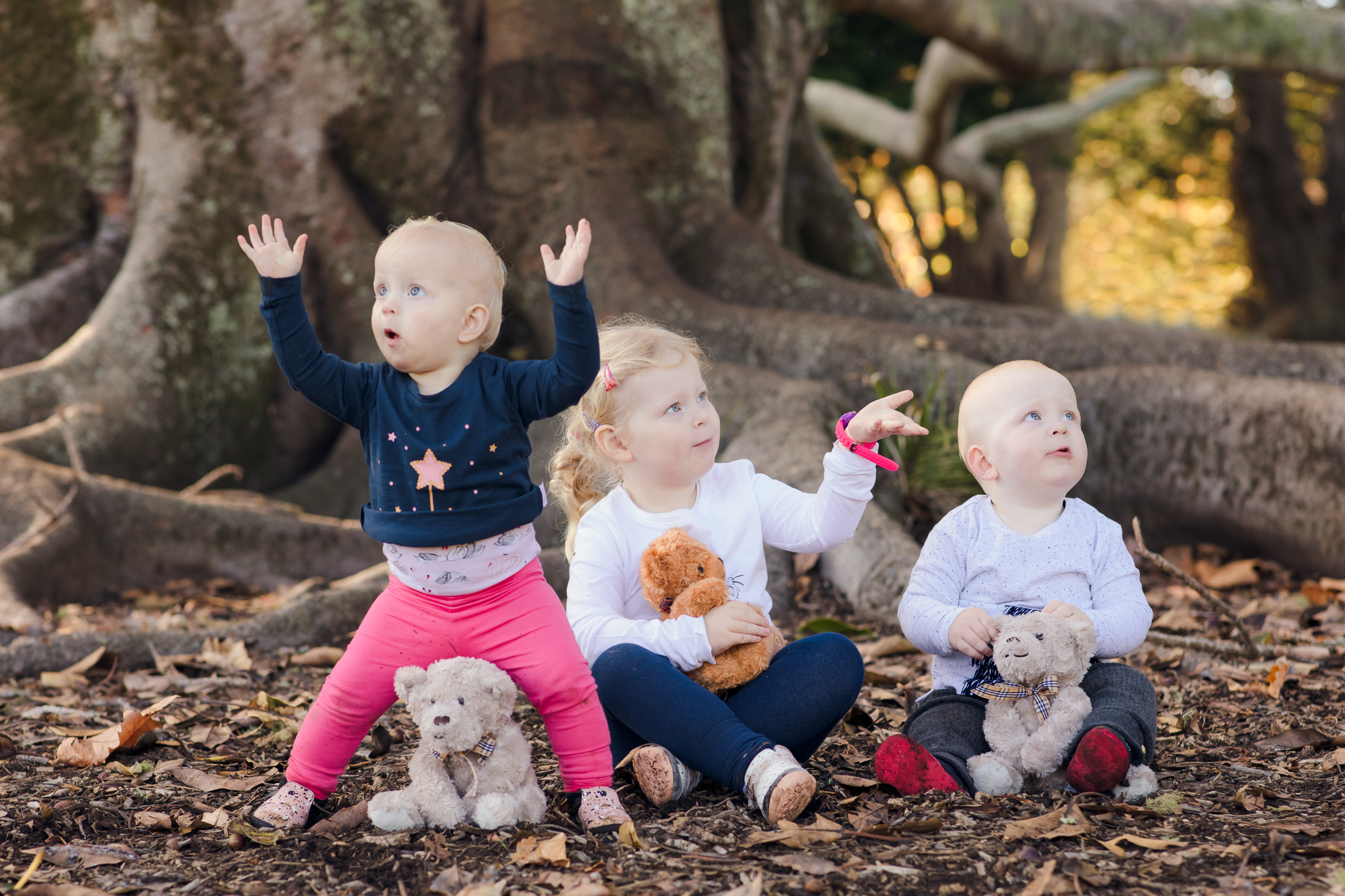 Big sister and twins sit by a tree at Cornwall park Auckland