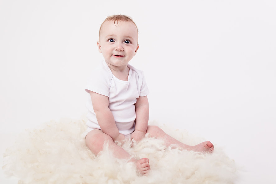 Baby wearing a white bodysuit sitting up and looking at the camera with a cute little smile taken by baby photographer Janine Fox photography