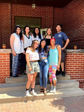 2019 DITA Cohort poses arm-in-arm for a photo outside a brick building.