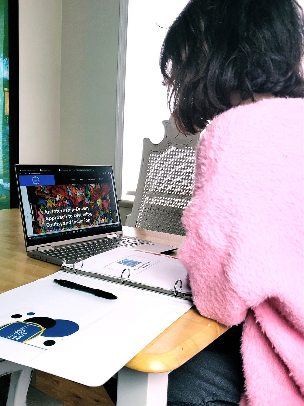 An individual sits at a kitchen table with a DITA binder in front of them along with a laptop open to the DITA website.