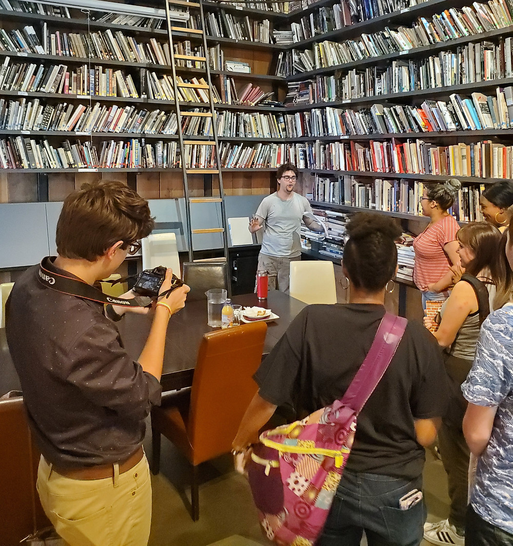 Interns stand in RedLine's community library with the hosting intern explaining the library to his cohort.