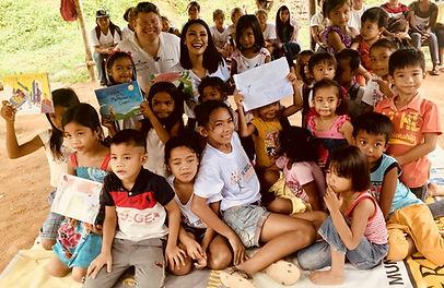 Dean Russell MP In Filipino Jungle reading his children's books to children in village