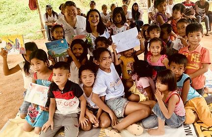 Dean Russell MP reading his children's books to children in the Philippine jungle village