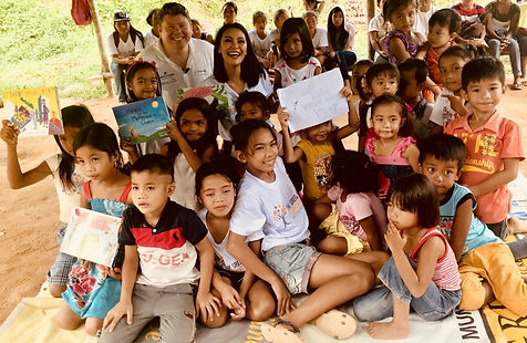 Dean Russell MP reading his children's books to children in the Philippine jungle village