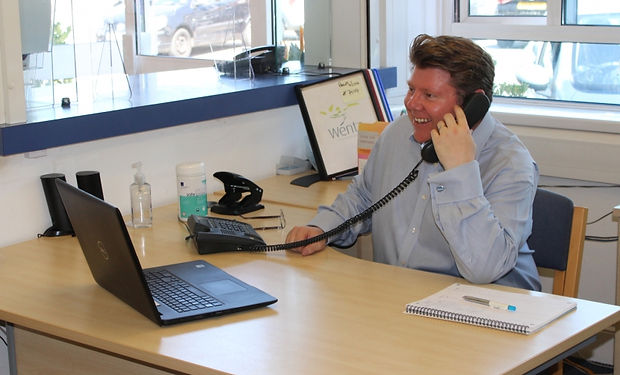 Dean Russell MP answering a phone at a desk in office as part of Put Dean On Your Team