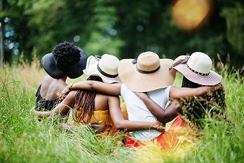 Back view  of group four gorgeous african american womans wear summer hat sitting at green