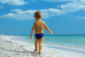 small baby boy walking the seaside. rear