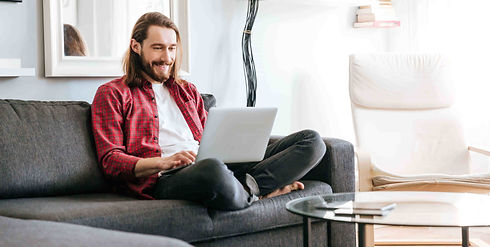 happy-man-sitting-sofa-using-laptop-home