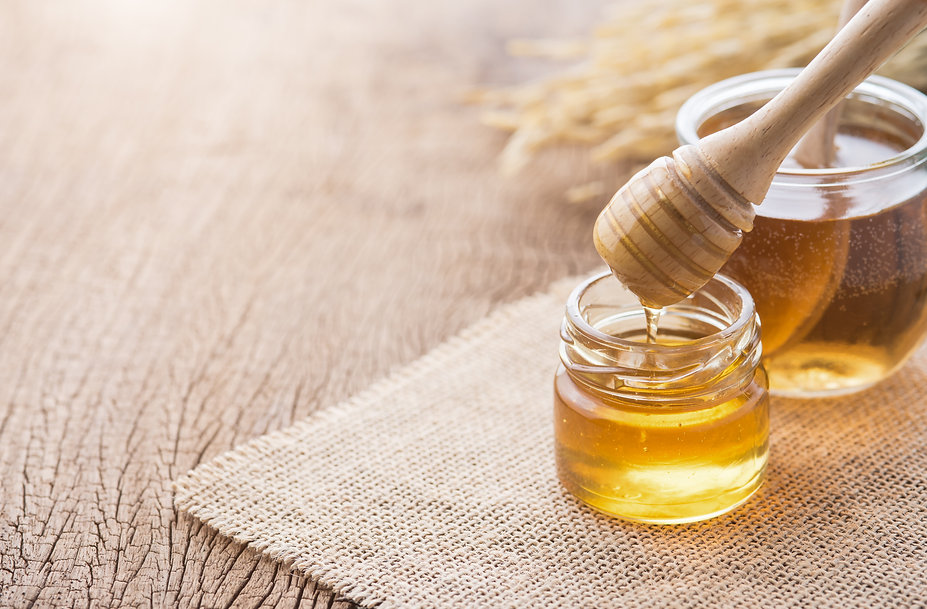 Honey with wooden honey dipper on wooden