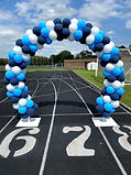 blue and white balloon arch at track school stadium in texas