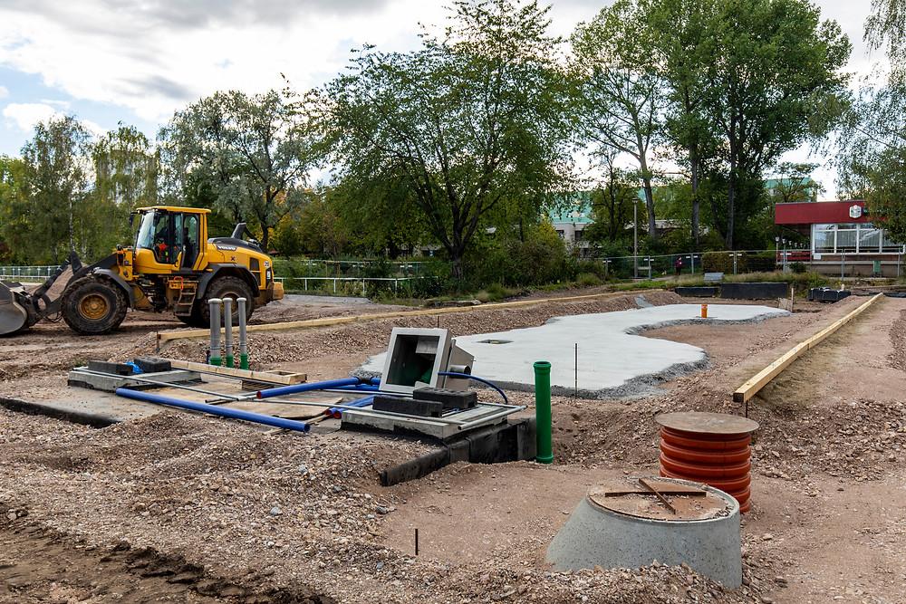 Baustelle eines zukünftigen Wasserspiels mit Bagger im Hintergrund