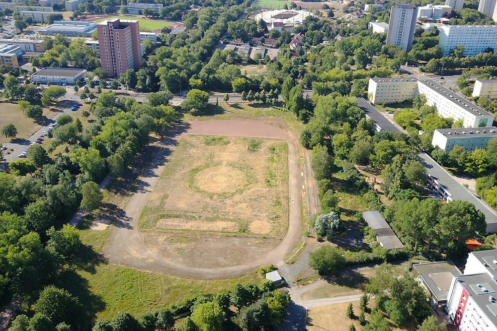 Lufaufnahme eines Wohngebiets, in der Mitte ein Park mit Sportplatz