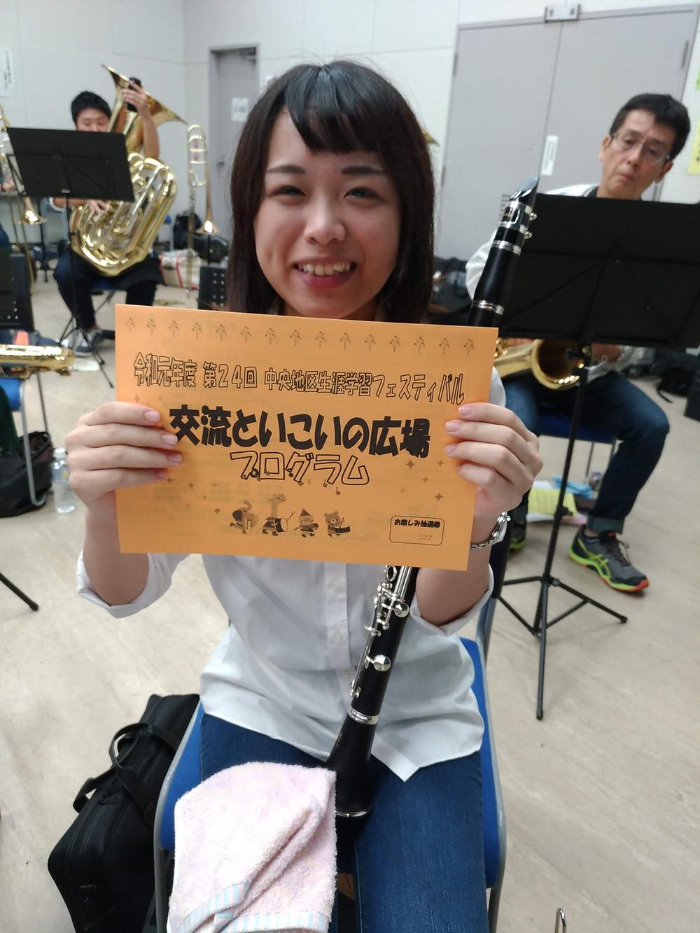 プログラムを片手に持つクラリネット奏者